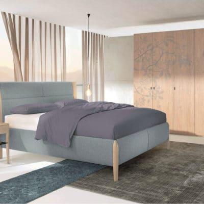 Schlafzimmer Mevisto mit Kleiderschrank, Bett und Nachttisch in Asteiche gebürstet weiß geölt, Bett Polsterbezug Stoff blaugrau.